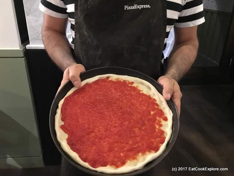 Pizza making adding sauce